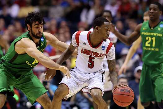 INDIANAPOLIS, IN - MARCH 29:  Kevin Ware #5 of the Louisville Cardinals handles the ball in the first half against Arsalan Kazemi #14 of the Oregon Ducks during the Midwest Region Semifinal round of the 2013 NCAA Men's Basketball Tournament at Lucas Oil Stadium on March 29, 2013 in Indianapolis, Indiana. Photo: Streeter Lecka, Getty Images / 2013 Getty Images