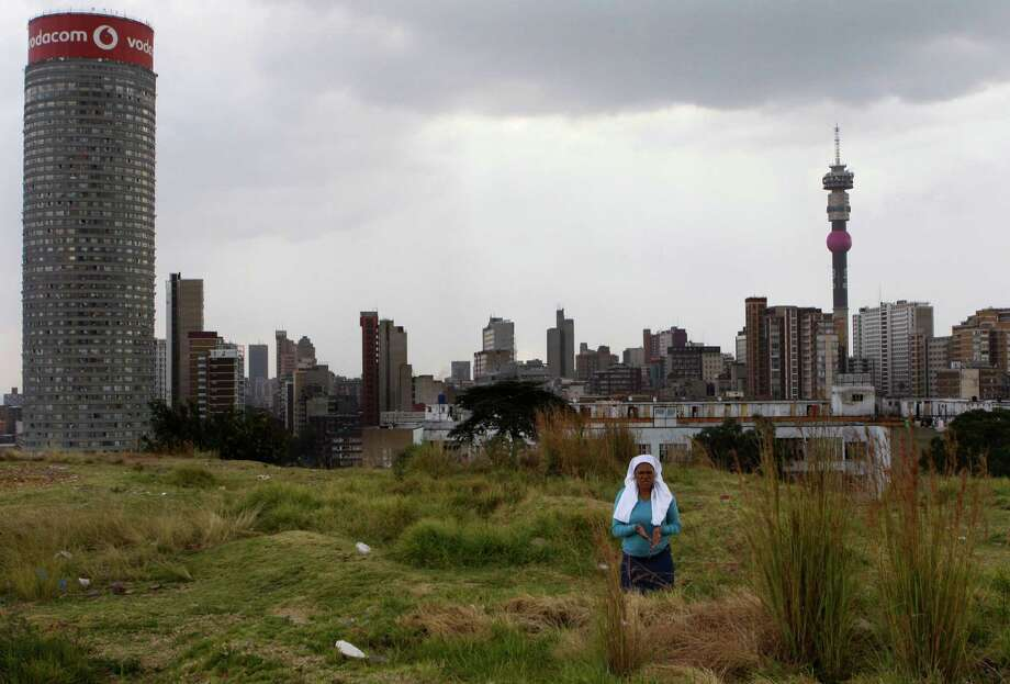 """A worshipper atop a hill overlooking Johannesburg offers Good Friday prayers and prayers for the quick recovery of former president Nelson Mandela Friday, March 29, 2013.   A lung infection that has plagued Nelson Mandela has struck again, prompting doctors to admit the 94-year-old former president to a hospital late at night. The presidency said Friday that Mandela was making """"steady progress"""" during hospital care. (AP Photo/Denis Farrell) Photo: Denis Farrell"""