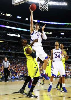 ARLINGTON, TX - MARCH 29:  Jeff Withey #5 of the Kansas Jayhawks shoots over Tim Hardaway Jr. #10 of the Michigan Wolverines in the first half during the South Regional Semifinal round of the 2013 NCAA Men's Basketball Tournament at Dallas Cowboys Stadium on March 29, 2013 in Arlington, Texas. Photo: Tom Pennington, Getty Images / 2013 Getty Images