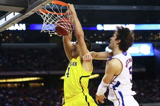 Michigan 87, Kansas 85 (OT)ARLINGTON, TX - MARCH 29:  Mitch McGary #4 of the Michigan Wolverines dunks past Jeff Withey #5 of the Kansas Jayhawks in the first half during the South Regional Semifinal round of the 2013 NCAA Men's Basketball Tournament at Dallas Cowboys Stadium on March 29, 2013 in Arlington, Texas. Photo: Ronald Martinez, Getty Images / 2013 Getty Images