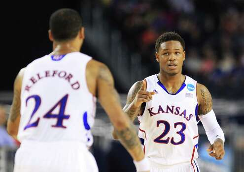 ARLINGTON, TX - MARCH 29:  Ben McLemore #23 celebrates with Travis Releford #24 of the Kansas Jayhawks in the first half against the Michigan Wolverines during the South Regional Semifinal round of the 2013 NCAA Men's Basketball Tournament at Dallas Cowboys Stadium on March 29, 2013 in Arlington, Texas. Photo: Ronald Martinez, Getty Images / 2013 Getty Images