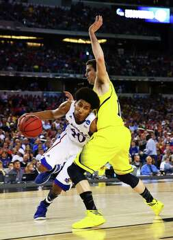 ARLINGTON, TX - MARCH 29:  Kevin Young #40 of the Kansas Jayhawks drives against Glenn Robinson III #1 of the Michigan Wolverines in the first half during the South Regional Semifinal round of the 2013 NCAA Men's Basketball Tournament at Dallas Cowboys Stadium on March 29, 2013 in Arlington, Texas. Photo: Tom Pennington, Getty Images / 2013 Getty Images