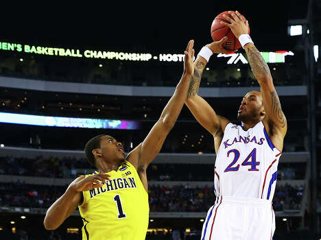 ARLINGTON, TX - MARCH 29:  Travis Releford #24 of the Kansas Jayhawks shoots over Glenn Robinson III #1 of the Michigan Wolverines in the first half during the South Regional Semifinal round of the 2013 NCAA Men's Basketball Tournament at Dallas Cowboys Stadium on March 29, 2013 in Arlington, Texas. Photo: Tom Pennington, Getty Images / 2013 Getty Images