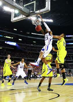 ARLINGTON, TX - MARCH 29:  Ben McLemore #23 of the Kansas Jayhawks dunks over Glenn Robinson III #1 and Jon Horford #15 of the Michigan Wolverines in the first half during the South Regional Semifinal round of the 2013 NCAA Men's Basketball Tournament at Dallas Cowboys Stadium on March 29, 2013 in Arlington, Texas. Photo: Tom Pennington, Getty Images / 2013 Getty Images