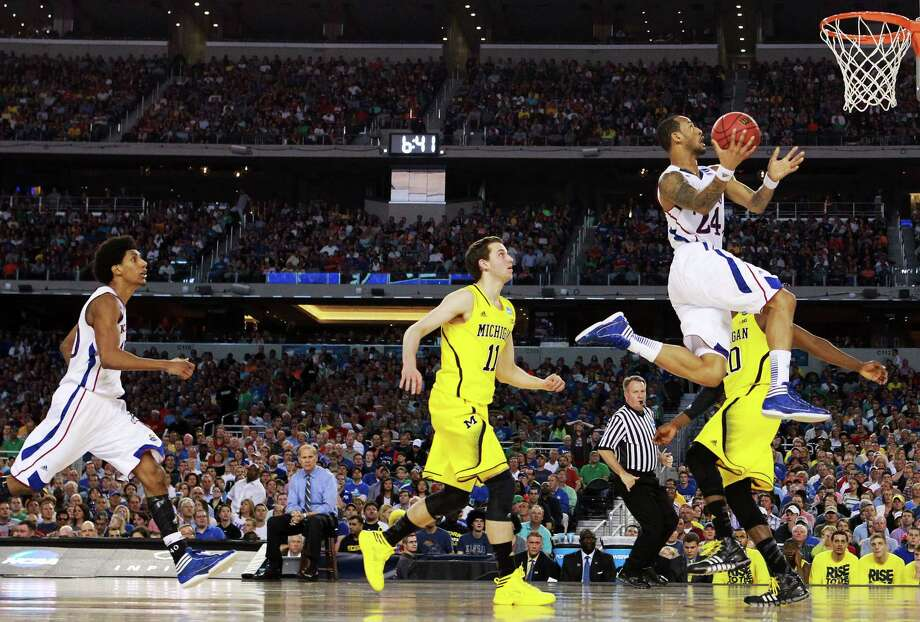 ARLINGTON, TX - MARCH 29:  Travis Releford #24 of the Kansas Jayhawks goes up against the Michigan Wolverines in the first half during the South Regional Semifinal round of the 2013 NCAA Men's Basketball Tournament at Dallas Cowboys Stadium on March 29, 2013 in Arlington, Texas. Photo: Ronald Martinez, Getty Images / 2013 Getty Images