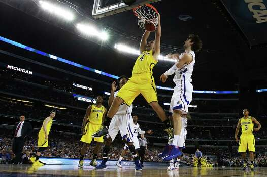 ARLINGTON, TX - MARCH 29:  Mitch McGary #4 of the Michigan Wolverines dunks pask Jeff Withey #5 of the Kansas Jayhawks in the first half during the South Regional Semifinal round of the 2013 NCAA Men's Basketball Tournament at Dallas Cowboys Stadium on March 29, 2013 in Arlington, Texas. Photo: Ronald Martinez, Getty Images / 2013 Getty Images