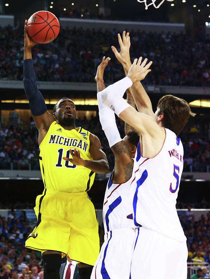 ARLINGTON, TX - MARCH 29:  Tim Hardaway Jr. #10 of the Michigan Wolverines shoots over Jeff Withey #5 of the Kansas Jayhawks in the first half during the South Regional Semifinal round of the 2013 NCAA Men's Basketball Tournament at Dallas Cowboys Stadium on March 29, 2013 in Arlington, Texas. Photo: Ronald Martinez, Getty Images / 2013 Getty Images