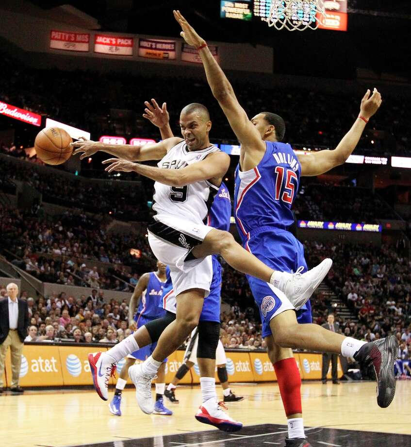 The Spurs' Tony Parker (9) makes a pass under the basket against Los Angeles Clippers' Ryan Hollins (15) in the first quarter at the AT&T Center on Friday, Mar. 29, 2013. Photo: Kin Man Hui, San Antonio Express-News / © 2012 San Antonio Express-News