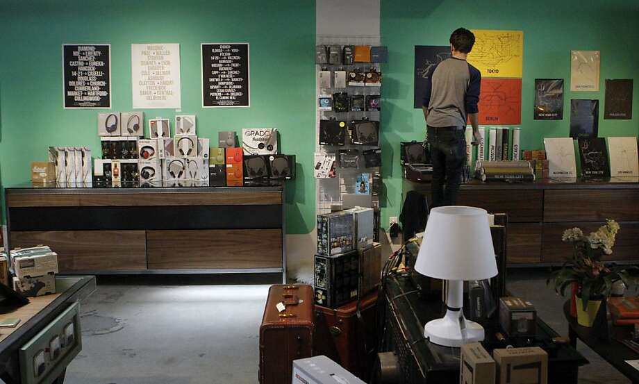 Trevor Grove straightens up posters at Dijital Fix, a store that opened in December in the Mission showcasing cutting-edge audio gear, clever wall art and repurposed retro pieces. Photo: Jessica Olthof, The Chronicle