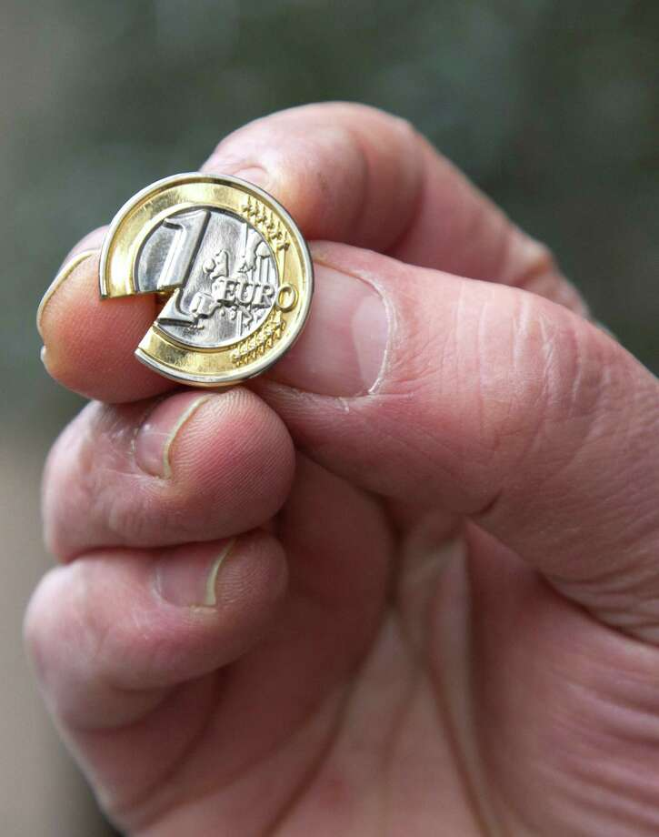 A Cypriot man, who did not wish to be identified, holds up a souvenir Cypriot euro coin lapel pin with a piece taken out near the Cypriot delegation building in Brussels on Sunday, March 24, 2013. The EU says a top official will chair a high-level meeting on Cyprus in a last-ditch effort to seal a deal before finance ministers decide whether the island nation gets a 10 billion euro bailout loan to save it from bankruptcy. (AP Photo/Virginia Mayo) Photo: Virginia Mayo