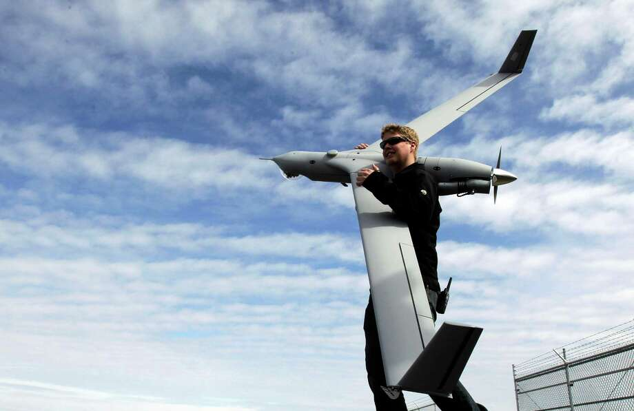 This photo taken March 26, 2013, shows flight test pilot Alex Gustafson carrying an InsituScanEagle unmanned aircraft in preparation for a flight in Arlington, Ore. It's a good bet that in the not-so-distant future aerial drones will be part of Americans' everyday lives, performing countless useful functions. A far cry from the killing machines whose missiles incinerate terrorists, these generally small unmanned aircraft will help farmers more precisely apply water and pesticides to crops, saving money and reducing environmental impacts. They'll help police departments to find missing people, reconstruct traffic accidents and act as lookouts for SWAT teams. They'll alert authorities to people stranded on rooftops by hurricanes, and monitor evacuation flows.  (AP Photo/Don Ryan) Photo: Don Ryan