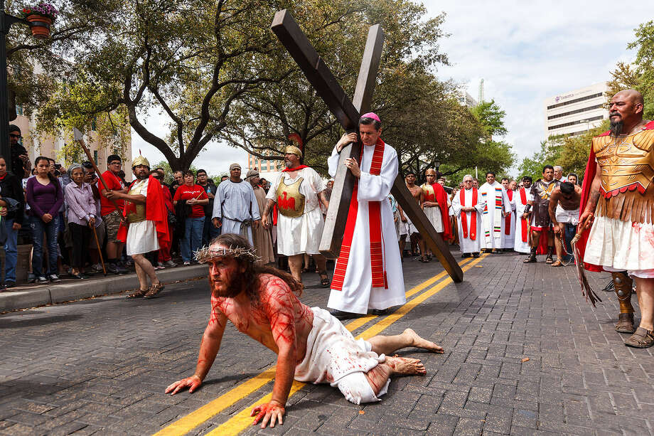 Jesus, played by John Austin, is helped by Simon of Cyrene, symbolized by Archbishop Gustavo García-Siller, after falling for the second time during the annual re-enactment of the Passion of the Christ downtown. Photo: Marvin Pfeiffer / San Antonio Express-News
