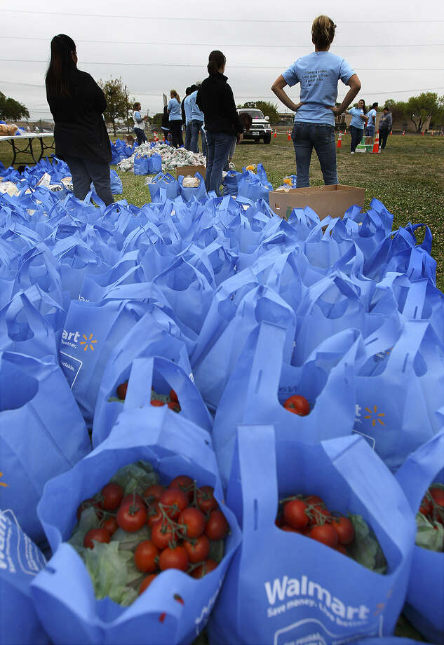 Bags of food are packed and ready to be distributed to needy families at Ross Middle School. Volunteers from Capital Group Cos. took part in a community action day at the school, which included distributing food via the Food Bank. Photo: Kin Man Hui / San Antonio Express-News