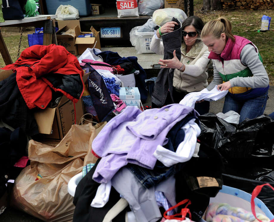 Patti Lansing, center right, and her daughter Julia, 17, sort clothes and other items donated for the Barth family, Friday, March 29, 2013. Fire destroyed the Berkshire Road home of Hans and Audra Barth and their three children in Newtown, Conn. Wednesday. Friends gathered at the home Friday, March 29, 2013, to offer support. The two Lansings teach religion in Peter Barth's First-grade class at St. Rose of Lima in Newtown. Photo: Carol Kaliff / The News-Times