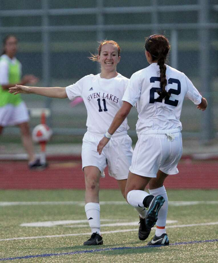 Seven Lakes' Caitlyn Mortus left, Junique Rodriguez right, celebrate after a Seven Lakes goal against Bellaire during the first half of a Class 5A bi-district girls soccer playoff game at Seven Lakes High School Friday, March 29, 2013, in Katy . Photo: James Nielsen, Houston Chronicle / © 2013 Houston Chronicle