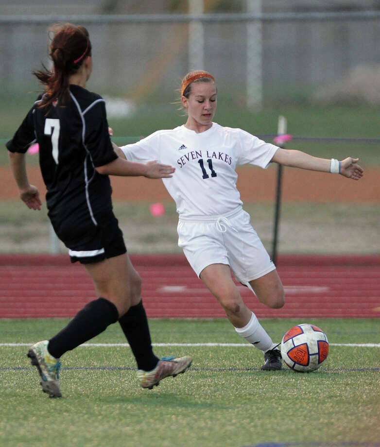 Seven Lakes' Caitlyn Mortus right kicks the ball past  Bellaire's Morgan Taper left, during the first half of a Class 5A bi-district girls soccer playoff game at Seven Lakes High School Friday, March 29, 2013, in Katy . Photo: James Nielsen, Houston Chronicle / © 2013 Houston Chronicle