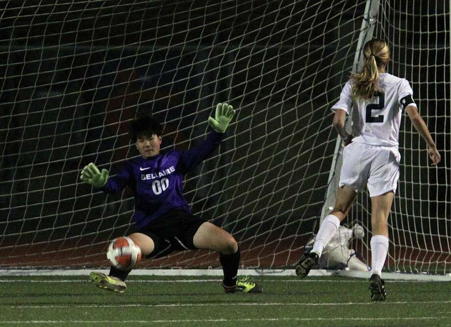 Seven Lakes' Sarah Eads right, watches as her shot passes Bellaire's goalkeeper Vivian Young left, to score a goal during the second half of a Class 5A bi-district girls soccer playoff game at Seven Lakes High School Friday, March 29, 2013, in Katy . Photo: James Nielsen, Houston Chronicle / © 2013 Houston Chronicle