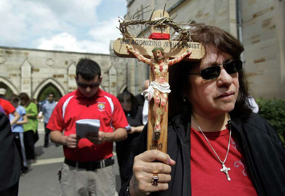 Eva Silvas holds a crucifix as people gather at Holy Rosary Catholic Church, 3617 Milam St., during the Way of the Cross walk Friday, March 29, 2013, in Houston. The walk hosted by the University of St. Thomas and Communion and Liberation, commemorates Christ's final walk through the streets of Jerusalem, carrying the Cross. Photo: Melissa Phillip, Houston Chronicle / © 2013  Houston Chronicle