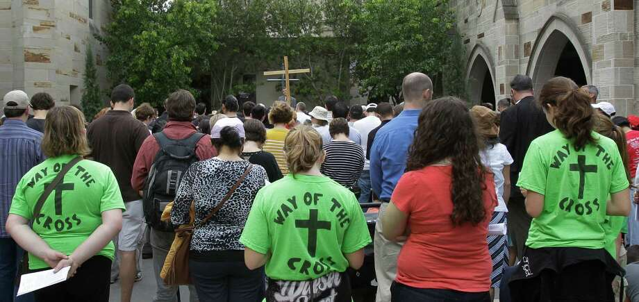 People gather at Holy Rosary Catholic Church, 3617 Milam St., during the Way of the Cross walk Friday, March 29, 2013, in Houston. The walk hosted by the University of St. Thomas and Communion and Liberation, commemorates Christ's final walk through the streets of Jerusalem, carrying the Cross. The 2.2 mile procession from the University of St. Thomas to the Co-Cathedral of the Sacred Heart included five stops to honor the passion of the cross. Photo: Melissa Phillip, Houston Chronicle / © 2013  Houston Chronicle
