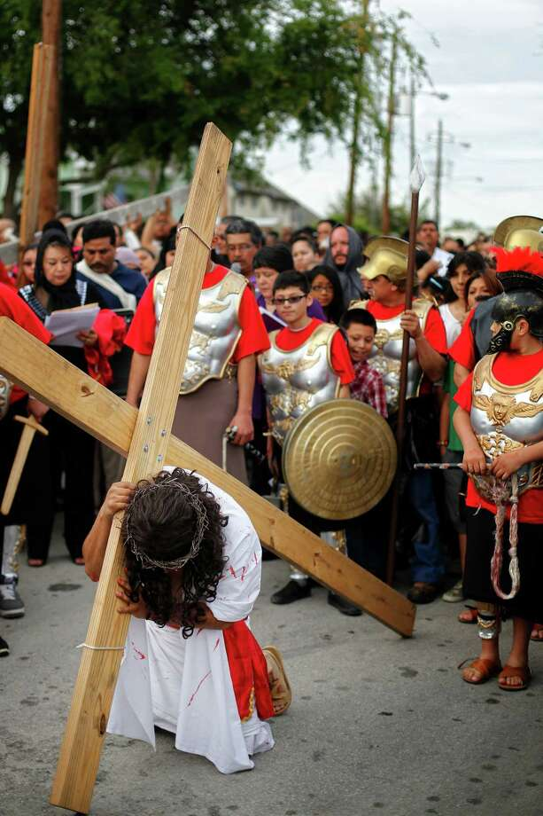 Jesus, played by Saul Perez, kneels as he is followed by a procession of the church, Friday, March 29, 2013, near Our Lady of Guadalupe Catholic church in Houston, Texas. Photo: TODD SPOTH, For The Chronicle / Todd Spoth