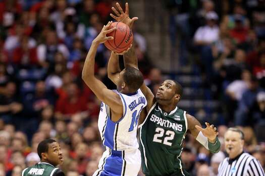 INDIANAPOLIS, IN - MARCH 29:  Branden Dawson #22 of the Michigan State Spartans defends against a shot attempt by Rasheed Sulaimon #14 of the Duke Blue Devils in the first half during the Midwest Region Semifinal round of the 2013 NCAA Men's Basketball Tournament at Lucas Oil Stadium on March 29, 2013 in Indianapolis, Indiana. Photo: Andy Lyons, Getty Images / 2013 Getty Images