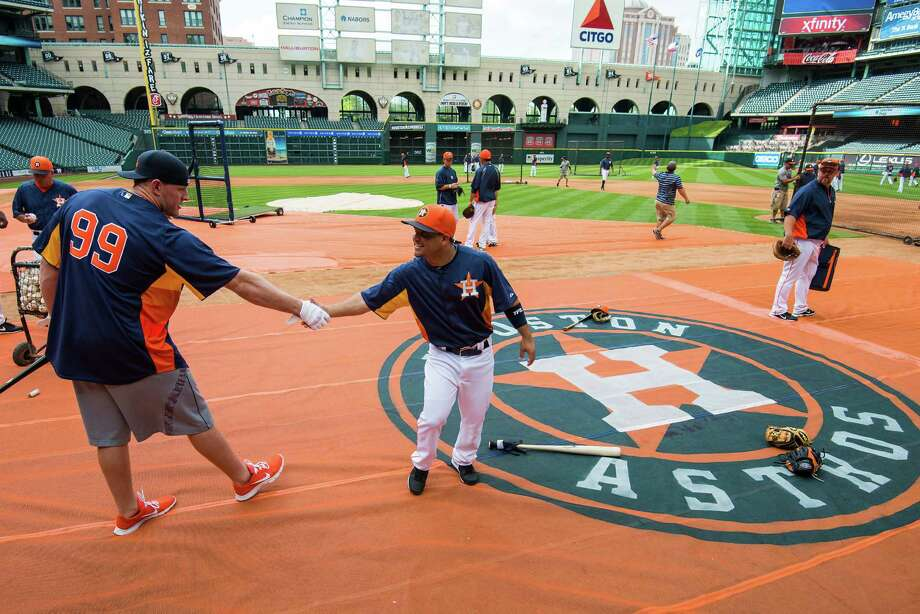 Texans defensive end J.J. Watt, who will throw out the first pitch in Sunday's opener, makes an adjustment to shake hands with Astros second baseman Jose Altuve, about a foot shorter and 120 pounds lighter. Photo: Smiley N. Pool / © 2013  Smiley N. Pool