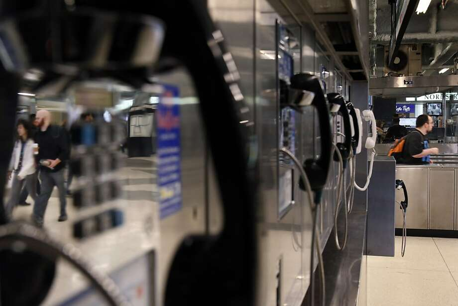 BART patrons are reflected as they walk past a row of seldom-used pay phones in the Powell Street Station. Photo: Carlos Avila Gonzalez, The Chronicle