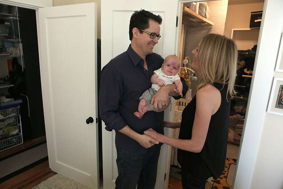 Kevin Ernst (left) with his two month old child Blake Ernst and wife Staci (right) talk about difficulties in converting their tenancy-in-common (TIC) unit into a condo in San Francisco, Calif., on Friday, February 15, 2013.  Blake lives in the closet and they presently want to sell to move into a place with a second bedroom. Photo: Liz Hafalia, The Chronicle