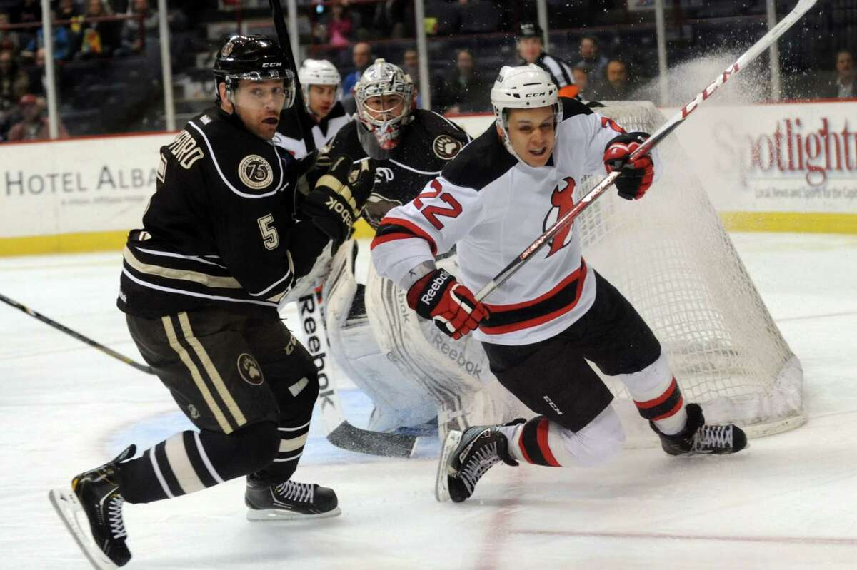 Devils' Jean-Sebastien Berube, right, and Bears' Garrett Stafford, left, apply the brakes to stop and chase a puck during their hockey game on Friday, March 29, 2013, at Times Union Center in Albany, N.Y. (Cindy Schultz / Times Union)