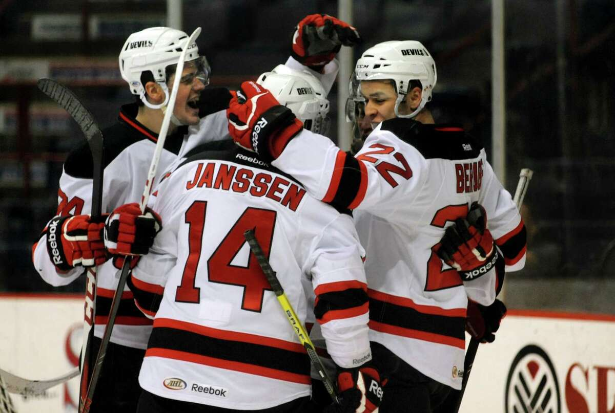 Devils' Eric Gelinas, left, celebrates a first-period goal by Cam Janssen, center, assisted by Jean-Sebastien Berube, right, during their hockey game against the Hershey Bears on Friday, March 29, 2013, at Times Union Center in Albany, N.Y. (Cindy Schultz / Times Union)