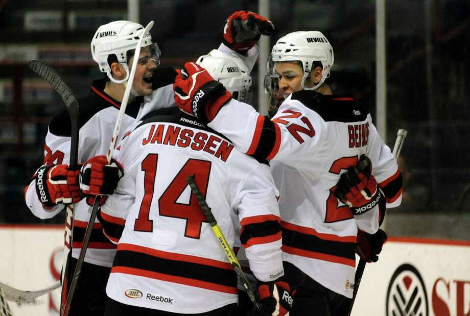 Devils' Eric Gelinas, left, celebrates a first-period goal by Cam Janssen, center, assisted by Jean-Sebastien Berube, right, during their hockey game against the Hershey Bears on Friday, March 29, 2013, at Times Union Center in Albany, N.Y. (Cindy Schultz / Times Union) Photo: Cindy Schultz / 00021748A