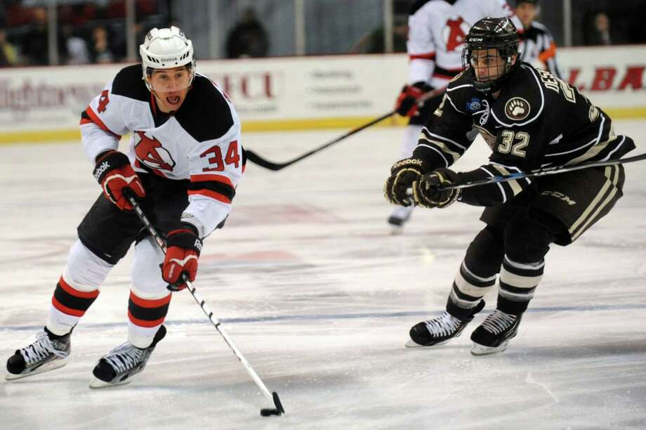 Devils' Phil DeSimone, left, controls the puck as Bears' Nicolas Deschamps defends during their hockey game on Friday, March 29, 2013, at Times Union Center in Albany, N.Y. (Cindy Schultz / Times Union) Photo: Cindy Schultz / 00021748A