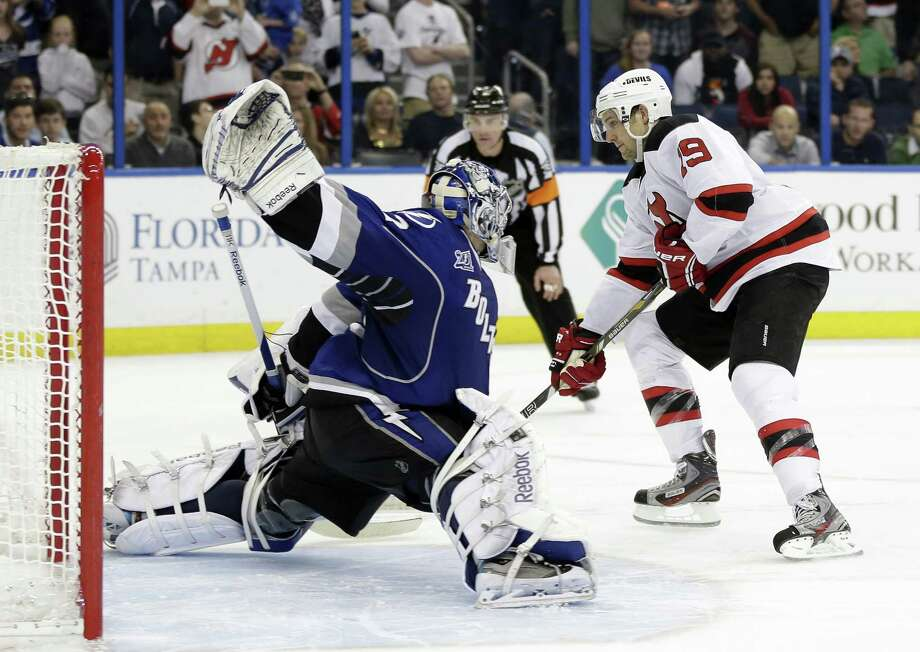 Tampa Bay Lightning goalie Mathieu Garon (32) stops New Jersey Devils center Travis Zajac (19) during a shootout in an NHL hockey game Friday, March 29, 2013, in Tampa, Fla. The Lightning won the game 5-4 in a shootout. (AP Photo/Chris O'Meara) Photo: Chris O'Meara