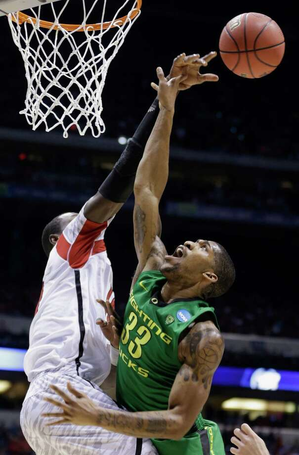 Louisville center Gorgui Dieng blocks a shot by Oregon forward Carlos Emory (33) during the second half of a regional semifinal in the NCAA college basketball tournament, Friday, March 29, 2013, in Indianapolis. Louisville won 77-69. (AP Photo/Michael Conroy) Photo: Michael Conroy