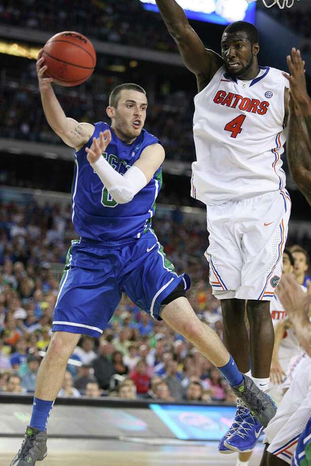 Florida Gulf Coast's Brett Comer passes underneath Florida's Patric Young (4) in the NCAA Tournament's Sweet 16 game at Cowboys Stadium in Arlington, Texas, on Friday, March 29, 2013. (Stephen M. Dowell/Orlando Sentinel/MCT) Photo: Stephen M. Dowell, McClatchy-Tribune News Service / Orlando Sentinel