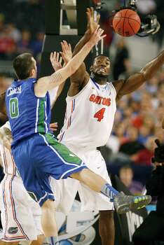 Florida's Patric Young (4) stops Florida Gulf Coast's Brett Comer (0) in the NCAA Tournament's Sweet 16 game at Cowboys Stadium in Arlington, Texas, on Friday, March 29, 2013. (Stephen M. Dowell/Orlando Sentinel/MCT) Photo: Stephen M. Dowell, McClatchy-Tribune News Service / Orlando Sentinel