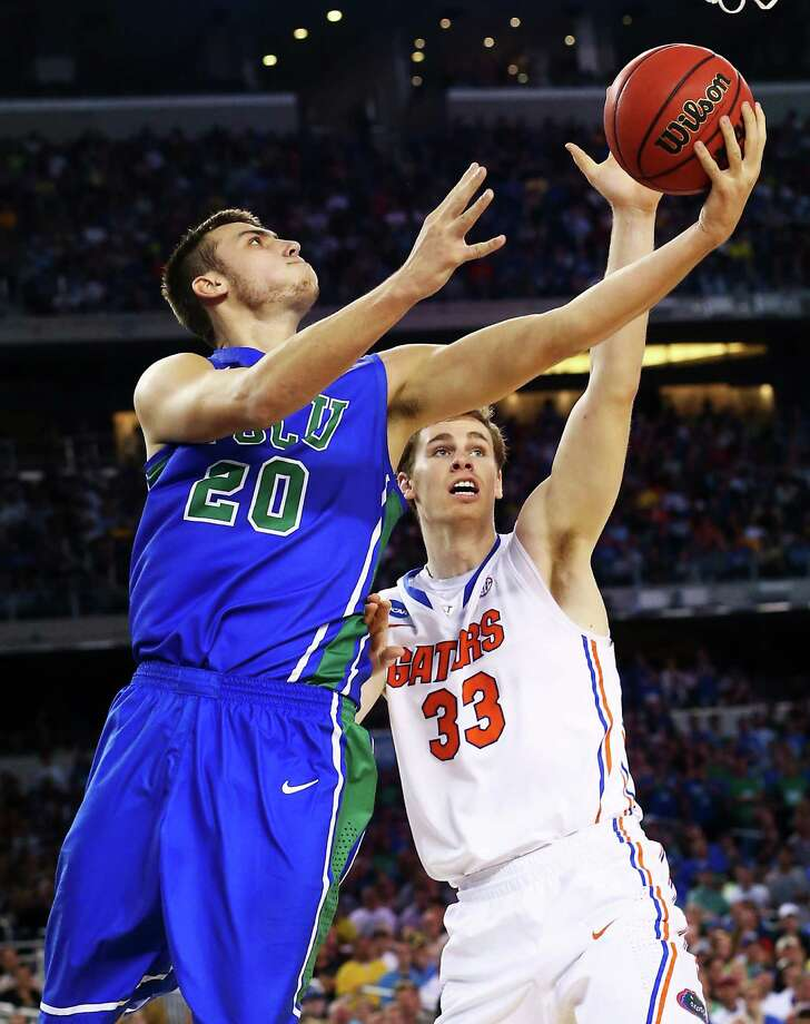 ARLINGTON, TX - MARCH 29:  Chase Fieler #20 of the Florida Gulf Coast Eagles goes up against Erik Murphy #33 of the Florida Gators in the first half during the South Regional Semifinal round of the 2013 NCAA Men's Basketball Tournament at Dallas Cowboys Stadium on March 29, 2013 in Arlington, Texas. Photo: Ronald Martinez, Getty Images / 2013 Getty Images