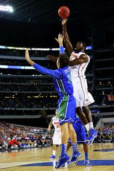 ARLINGTON, TX - MARCH 29:  Patric Young #4 of the Florida Gators shoots over Filip Cvjeticanin #15 of the Florida Gulf Coast Eagles in the first half during the South Regional Semifinal round of the 2013 NCAA Men's Basketball Tournament at Dallas Cowboys Stadium on March 29, 2013 in Arlington, Texas. Photo: Tom Pennington, Getty Images / 2013 Getty Images
