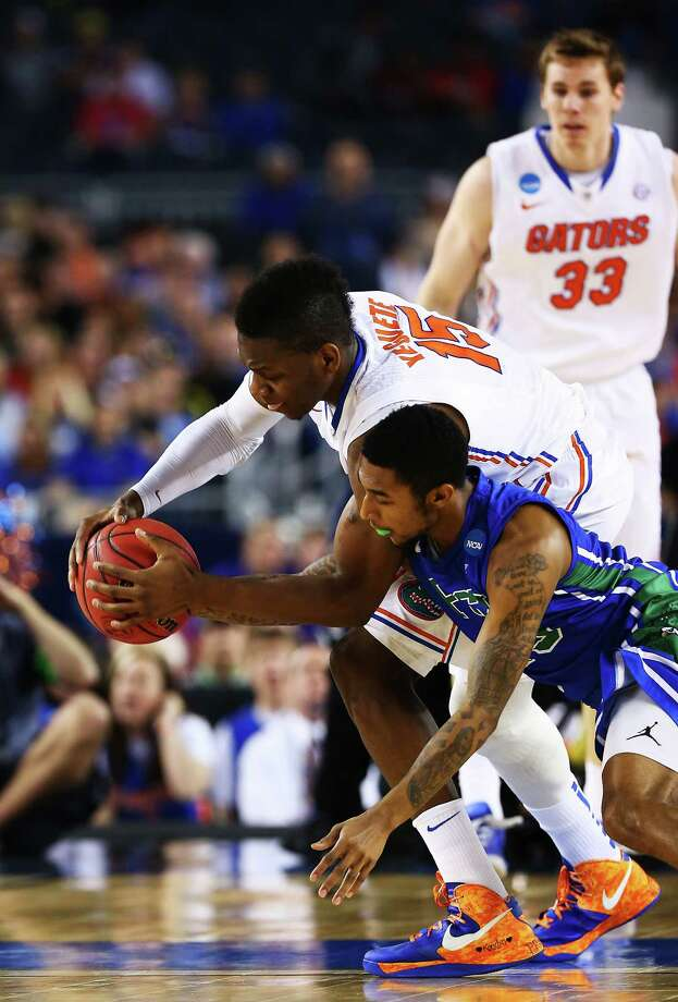 ARLINGTON, TX - MARCH 29:  Dajuan Graf #35 of the Florida Gulf Coast Eagles attempts to steal from Will Yeguete #15 of the Florida Gators in the first half during the South Regional Semifinal round of the 2013 NCAA Men's Basketball Tournament at Dallas Cowboys Stadium on March 29, 2013 in Arlington, Texas. Photo: Tom Pennington, Getty Images / 2013 Getty Images