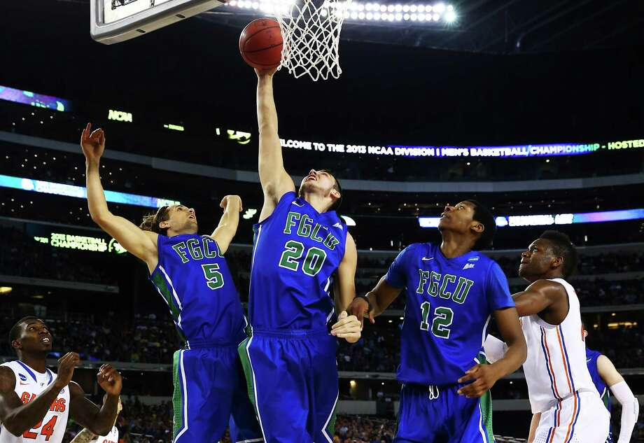 ARLINGTON, TX - MARCH 29:  Chase Fieler #20 rebounds between Christophe Varidel #5 and Eric McKnight #12 of the Florida Gulf Coast Eagles in the first half against the Florida Gators during the South Regional Semifinal round of the 2013 NCAA Men's Basketball Tournament at Dallas Cowboys Stadium on March 29, 2013 in Arlington, Texas. Photo: Tom Pennington, Getty Images / 2013 Getty Images