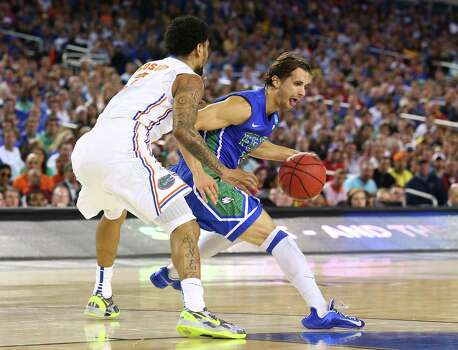 ARLINGTON, TX - MARCH 29:  Christophe Varidel #5 of the Florida Gulf Coast Eagles drives on Mike Rosario #3 of the Florida Gators in the first half during the South Regional Semifinal round of the 2013 NCAA Men's Basketball Tournament at Dallas Cowboys Stadium on March 29, 2013 in Arlington, Texas. Photo: Ronald Martinez, Getty Images / 2013 Getty Images