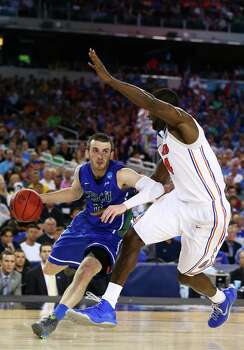 ARLINGTON, TX - MARCH 29:  Brett Comer #0 of the Florida Gulf Coast Eagles drives against Patric Young #4 of the Florida Gators in the first half during the South Regional Semifinal round of the 2013 NCAA Men's Basketball Tournament at Dallas Cowboys Stadium on March 29, 2013 in Arlington, Texas. Photo: Ronald Martinez, Getty Images / 2013 Getty Images