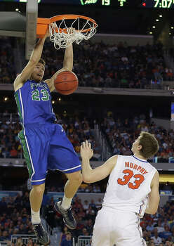Florida Gulf Coast's Eddie Murray (23) dunks as Florida's Erik Murphy (33) defends during the first half of a regional semifinal game in the NCAA college basketball tournament, Friday, March 29, 2013, in Arlington, Texas. (AP Photo/Tony Gutierrez) Photo: Tony Gutierrez, Associated Press / AP