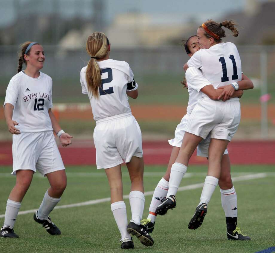 Seven Lakes' Jenna Marotta (12), Sarah Eads (2) and Junique Rodriguez celebrate Caitlyn Mortus' (11) first-half goal against Bellaire on Friday night. Photo: James Nielsen, Staff / © 2013 Houston Chronicle