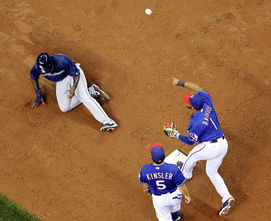 Texas Rangers' Elvis Andrus turns a double play as San Diego Padres' Cameron Maybin slides into second base as teammate Texas Rangers' Ian Kisler looks on during the fifth inning of an exhibition baseball game part of the �Big League Weekend� Friday March 29, 2013 at the Alamodome. Photo: Edward A. Ornelas, Express-News / © 2013 San Antonio Express-News