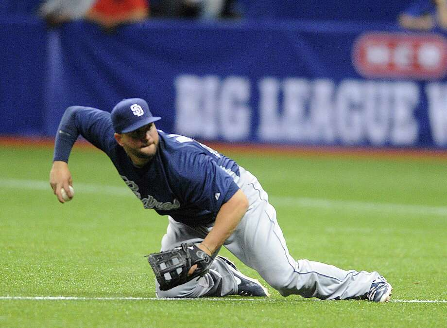 San Diego first baseman Yonder Alonso dives to catch a ground ball but is unable to throw to first base in time to get the runner out during Big League Weekend at the Alamodome on Friday, March 29, 2013. Photo: Billy Calzada, Express-News / San Antonio Express-News