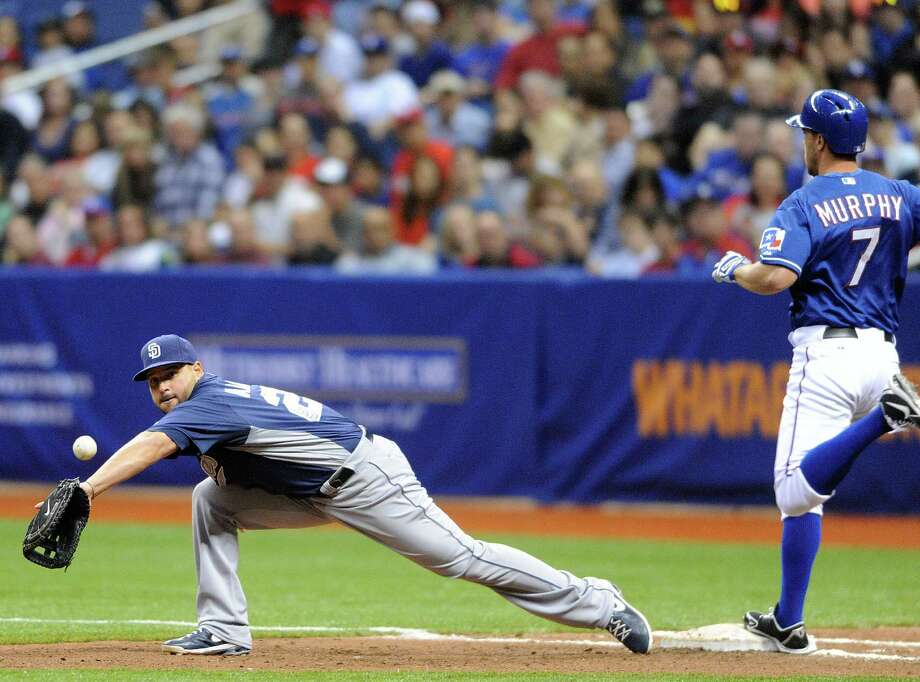 Texas runner David Murphy beats a throw to first as San Diego first baseman Yonder Alonso stretches for the ball during Big League Weekend at the Alamodome on Friday, March 29, 2013. Photo: Billy Calzada, Express-News / San Antonio Express-News