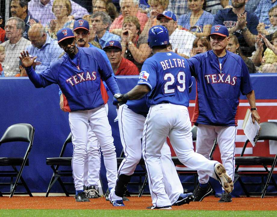 Texas Rangers manager Ron Washington, left, greets Adrian Beltre after Beltre scored during Big League Weekend exhibition action against the San Diego Padres at the Alamodome on Friday, March 29, 2013. Photo: Billy Calzada, Express-News / San Antonio Express-News