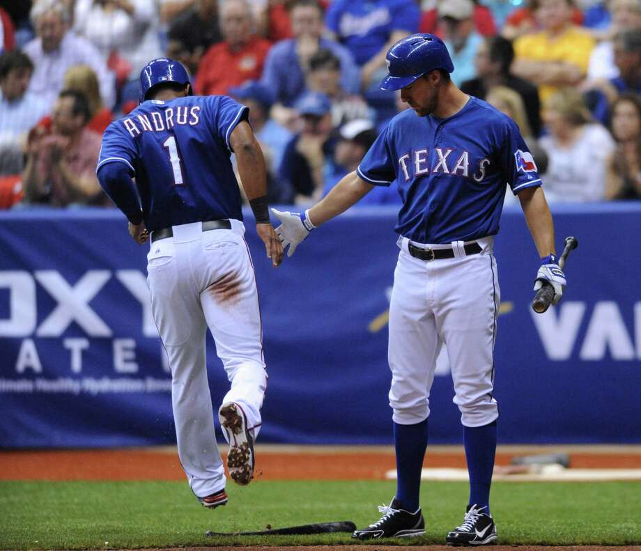 Elvis Andrus of the Texas Ranges is greeted by teammate David Murphy after scoring on a sacrifice fly in the bottom of the 4th inning during Big League Weekend at the Alamodome on Friday, March 29, 2013. The Rangers and Padres played the first-ever baseball game in the Alamodome. A second game will be played on Saturday afternoon. Photo: Billy Calzada, Express-News / San Antonio Express-News