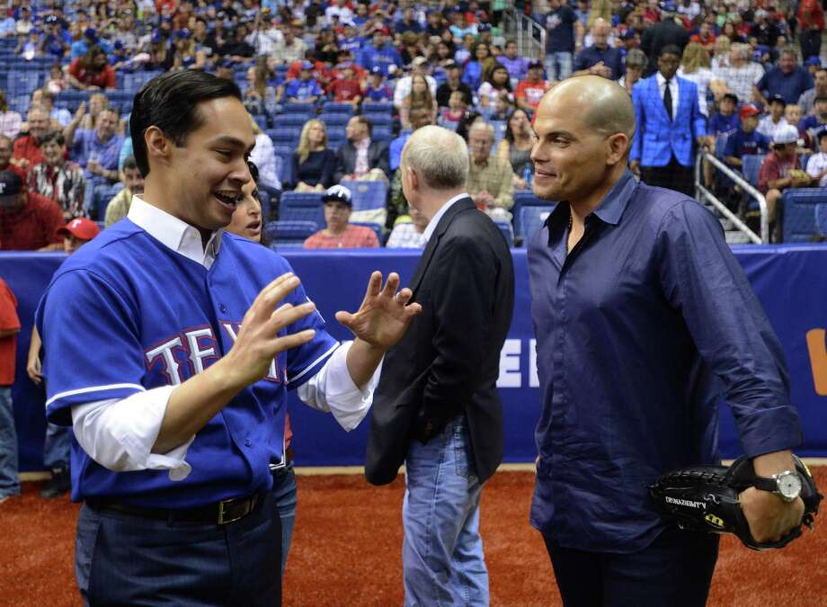 San Antonio Mayor Julian Castro jokes with former Texas Rangers catcher Ivan Rodriguez before the Big League Weekend at the Alamodome on Friday, March 29, 2013. Photo: Billy Calzada, Express-News / San Antonio Express-News
